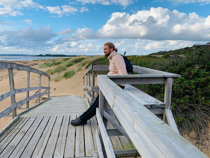 Man sitting on wooden railing against sky