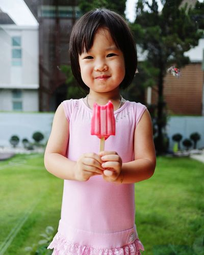 Portrait Of Smiling Cute Girl Holding Ice Cream