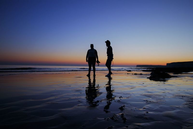 Silhouette man and woman on beach against sky during sunset