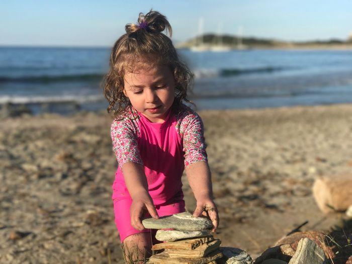 Close-up of girl stacking rocks at beach