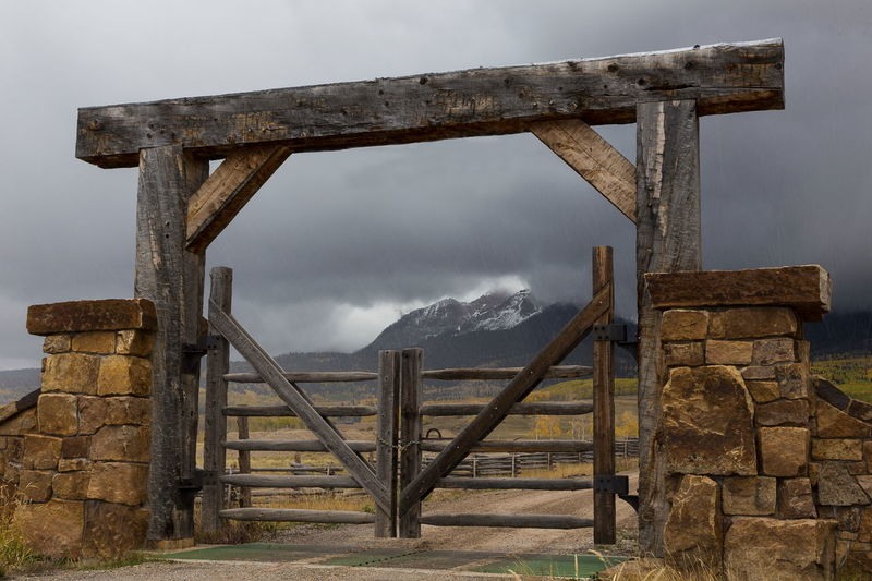 Wooden chained ranch gate and stone pillars against background of mountains in dark cloudy weather, Colorado Ranch Gate Wooden Stone Pillars Mountains Colorado Dark Cloudy Skies Chained Landscape Cloud - Sky Mountain Wood - Material Entrance Gate Dirt Road Padlocked Deserted Forbidding Autumn Fall Grey Sky