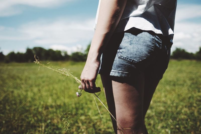 Midsection of woman wearing shorts walking on grassy field