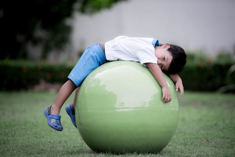 Cute boy lying on fitness ball at field