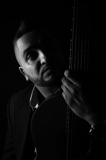 Man with guitar against black background