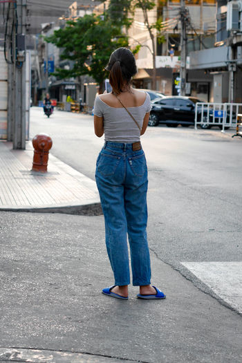 Rear view of woman standing on footpath in city
