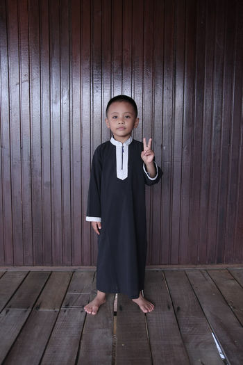 Portrait of boy showing peace sign while standing against wooden wall