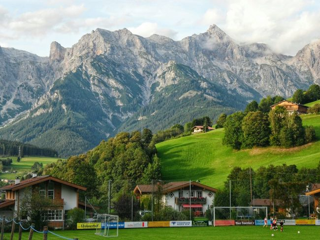 Maria Alm. Maria Alm Maria Alm Am Steinernen Meer Austria Alpen Alpi Montagna Nature Football Field Mountains And Valleys ES75 Mountain Building Exterior Sky Mountain Range No People Green Color Cloud - Sky Tree Architecture Growth Landscape Outdoors Beauty In Nature Scenics Day