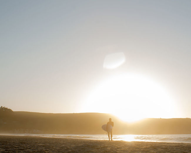 Silhouette man carrying surfboard at beach during sunset
