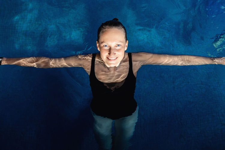 High angle view of smiling woman in swimming pool