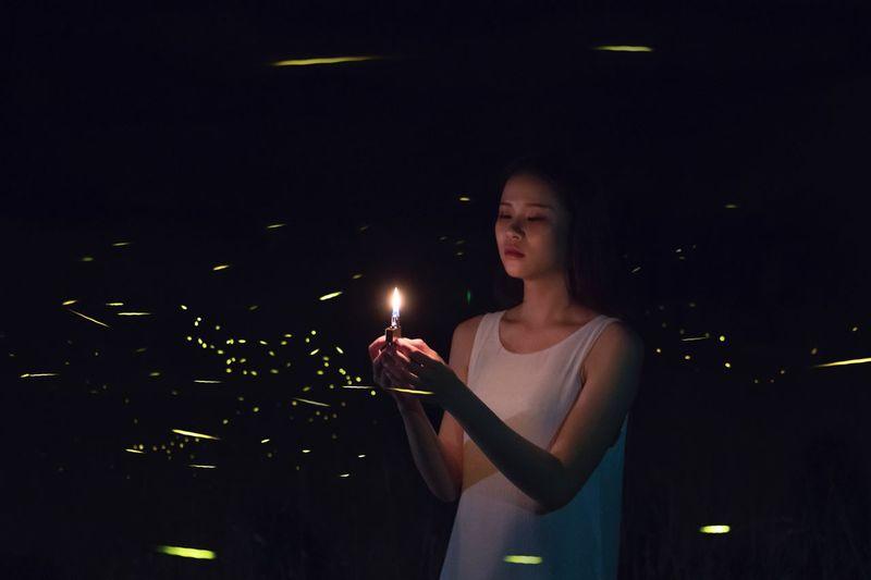 Young woman looking away at night