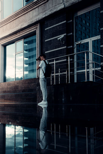 Reflection of person on glass window in building