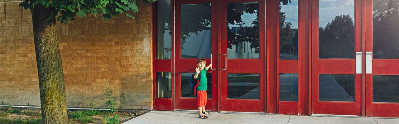 Full length of boy with backpack standing by door