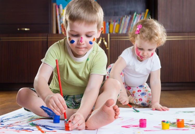 Cute kids painting on paper while sitting at home