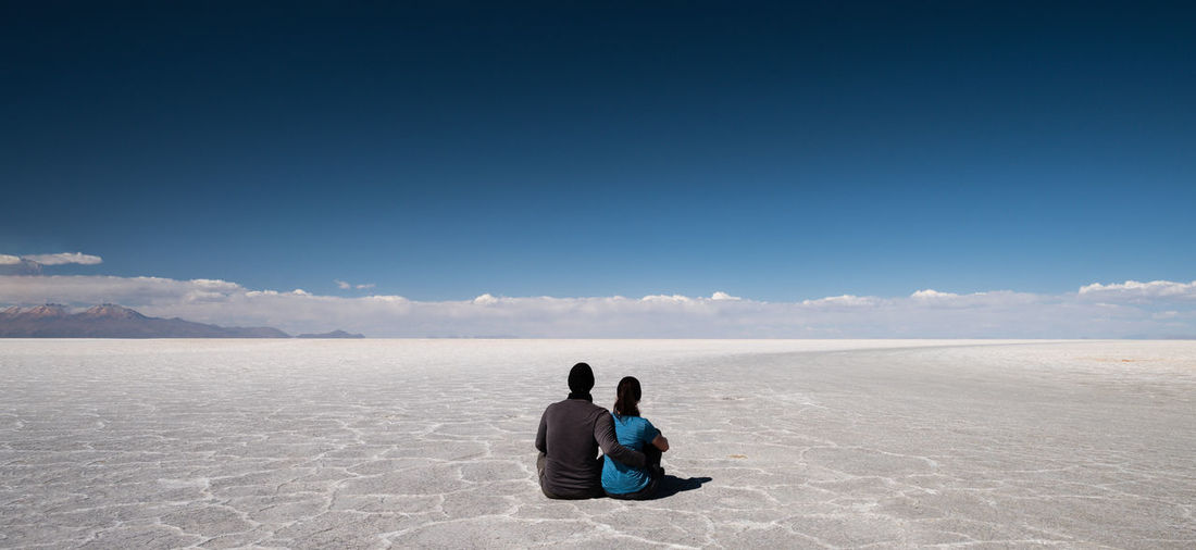 Uyuni Salt flats in Bolivio, what a geat adventure we had there. Connected By Travel Uyuni Adult Adults Only Arid Climate Beauty In Nature Blue Copy Space Day Desert Full Length Landscape Mature Adult Mature Men Men Outdoors People Salt Flat Sand Scenics Sitting Sky Togetherness Wireless Technology Women