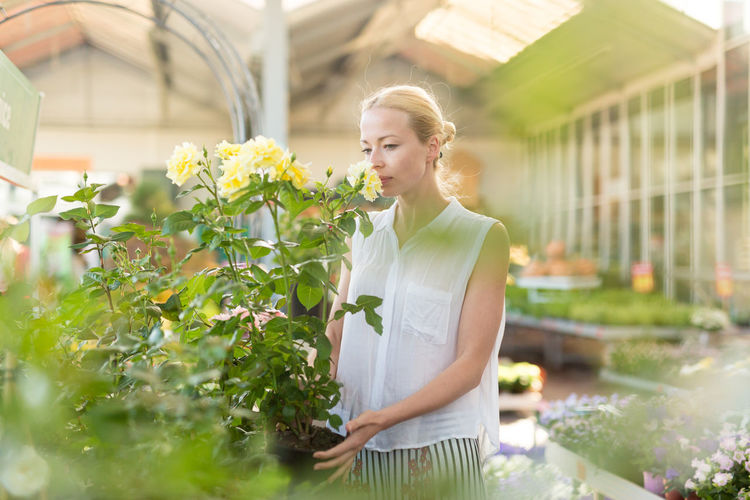 Woman looking at camera while standing by plants