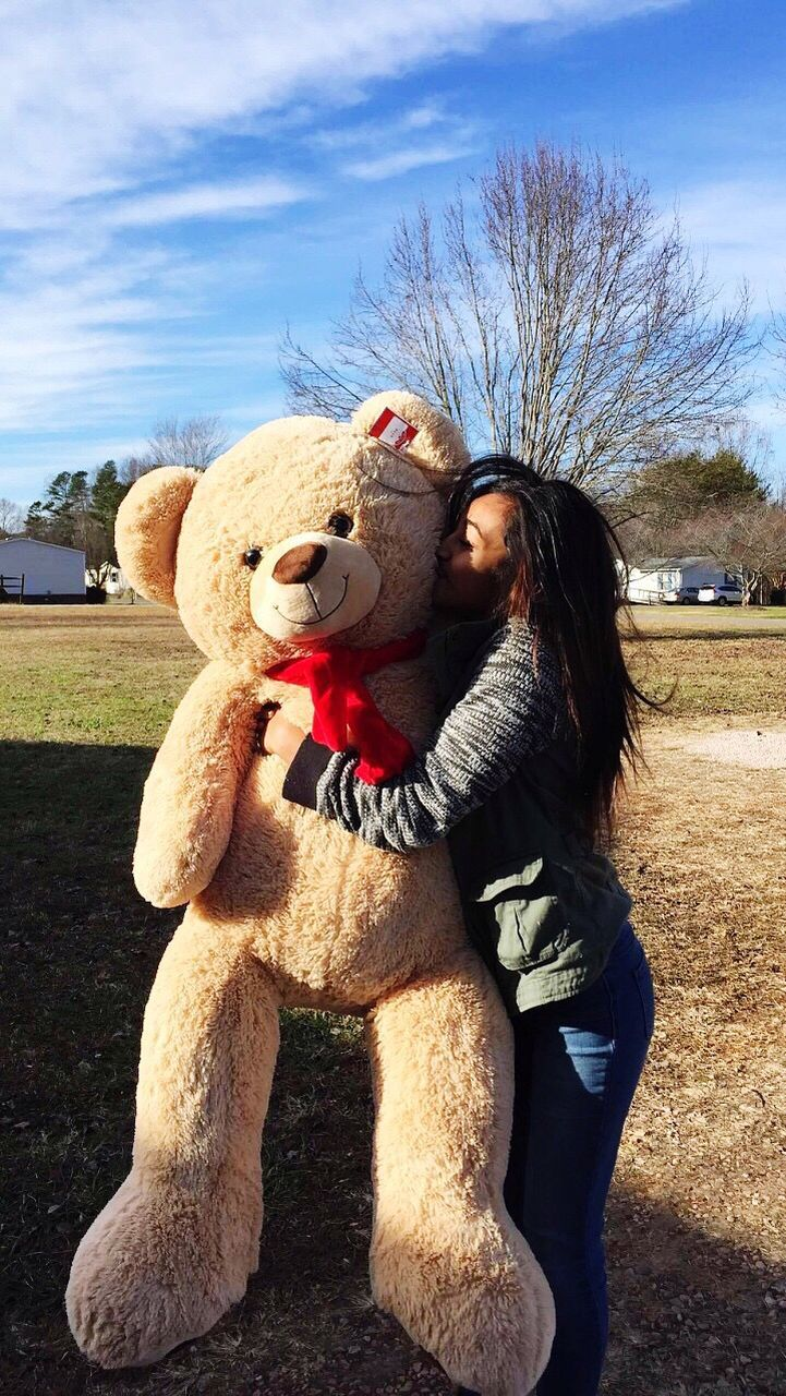 stuffed toy, teddy bear, one person, animal representation, field, day, real people, childhood, sky, leisure activity, smiling, tree, happiness, outdoors, young women, young adult, people