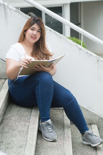 Full length portrait of young woman holding book while sitting on steps