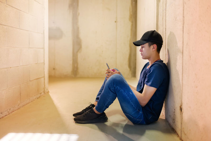 Side view of young man using phone while sitting on wall
