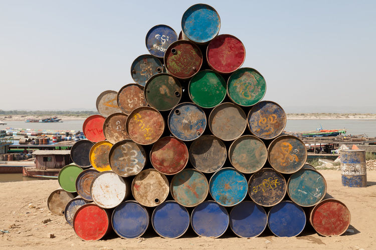 Stack Of Multi Colored Rusty Barrels At Beach Against Sky
