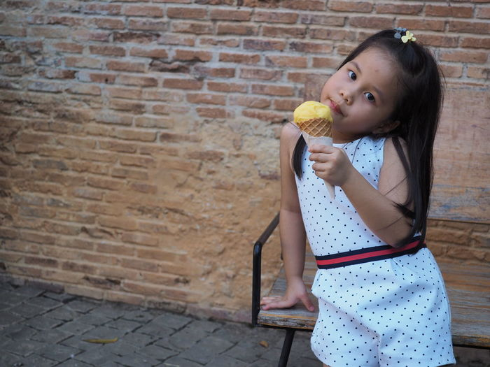 Portrait of girl holding ice cream against brick wall