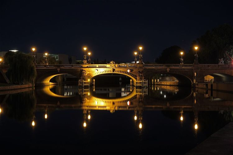 Illuminated Moltke Bridge Over Spree River Against Clear Sky At Night