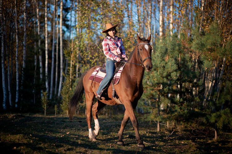 A woman wearing a cowboy hat rides a horse in a countryside farm yard,natural soft sunlight