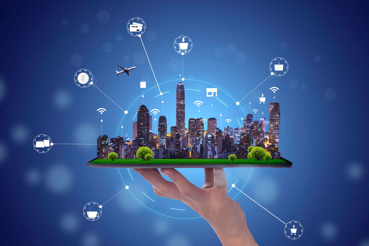 Digital composite image of hand holding city against blue sky