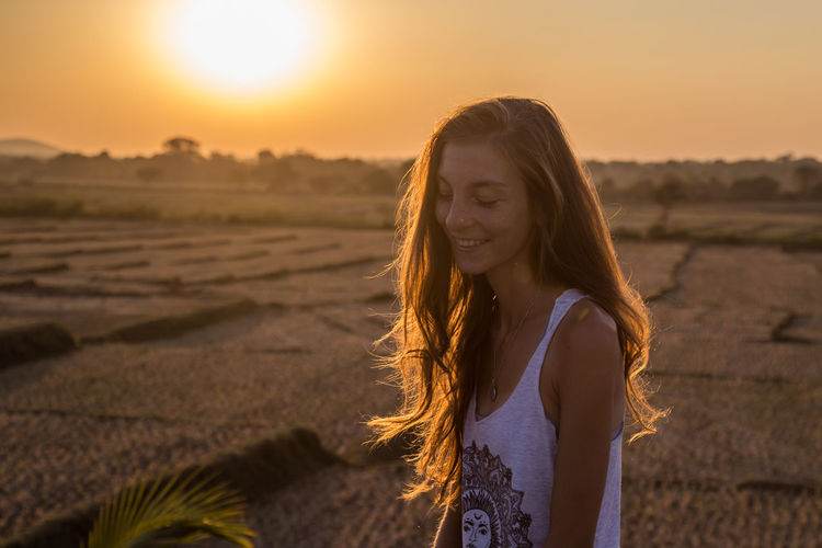Portrait of beautiful young woman against sunset sky