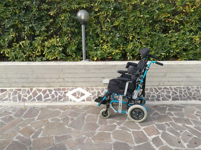 Empty wheelchair on footpath by plants