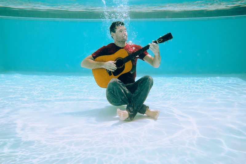 Man playing guitar underwater