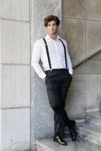 Man wearing suspenders while standing by wall