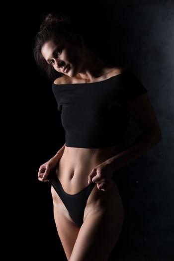 Portrait of woman wearing bikini standing indoors