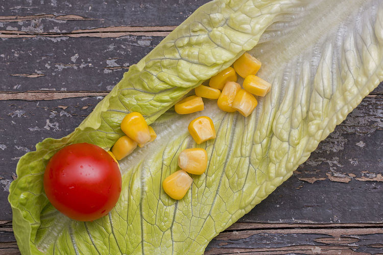 A cherry tomato and some corn grains on a lettuce leaf. Cherry Diet Vegetarian Corn Food Freshness Green Color Healthy Leaf Lettuce Raw Food Red Still Life Summer Sweetcorn Table Tomato Vegan Vegetable Wood - Material Yellow