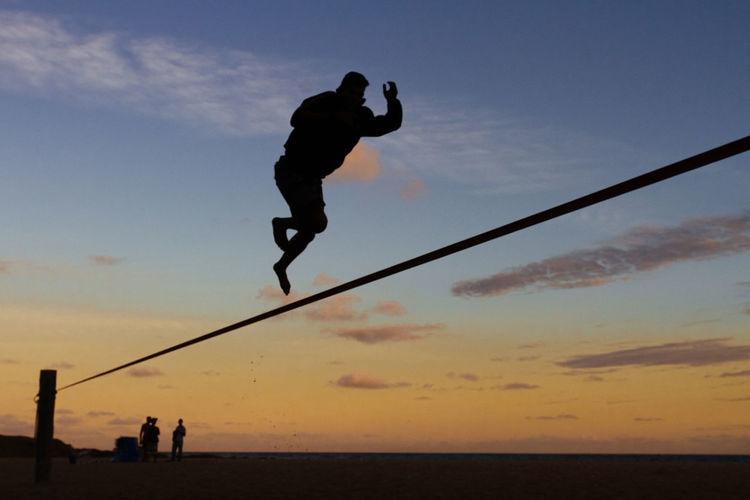 Silhouette man jumping in sea against sky during sunset