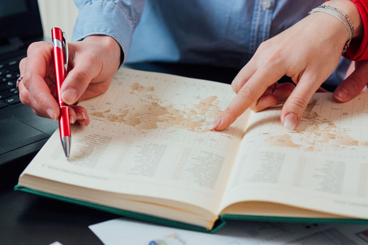 Midsection of woman reading book on table