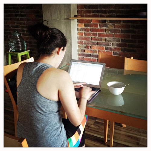 Woman working at home on a laptop. Woman Working Working From Home Typing Laptop Cellphone Dining Table Eating