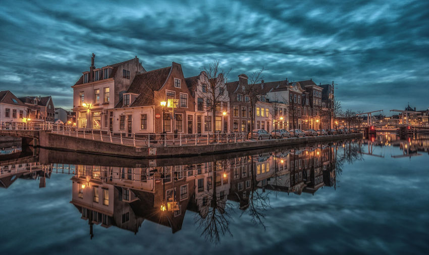 Illuminated buildings by river against cloudy sky at dusk