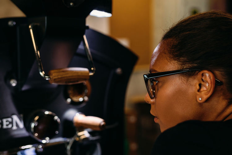 Side View Of Thoughtful Young Woman Wearing Eyeglasses In Cafe