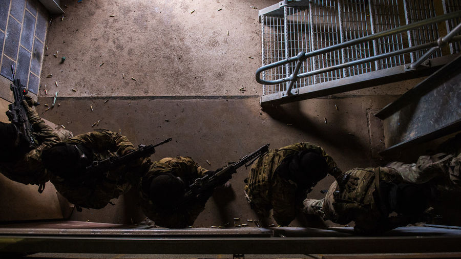 Directly Above Shot Of Army Soldiers With Rifles In Abandoned Building