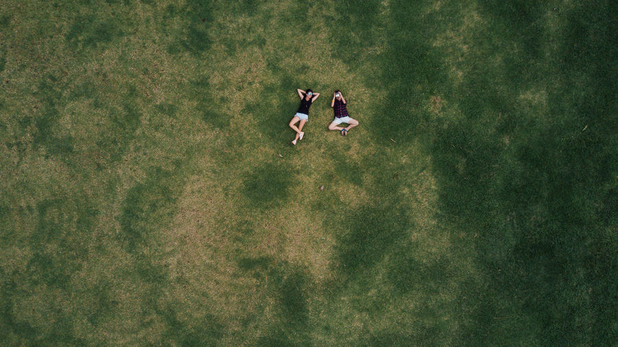High Angle View Of Women Lying In Grass