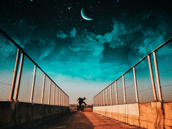 Man jumping on bridge against sky