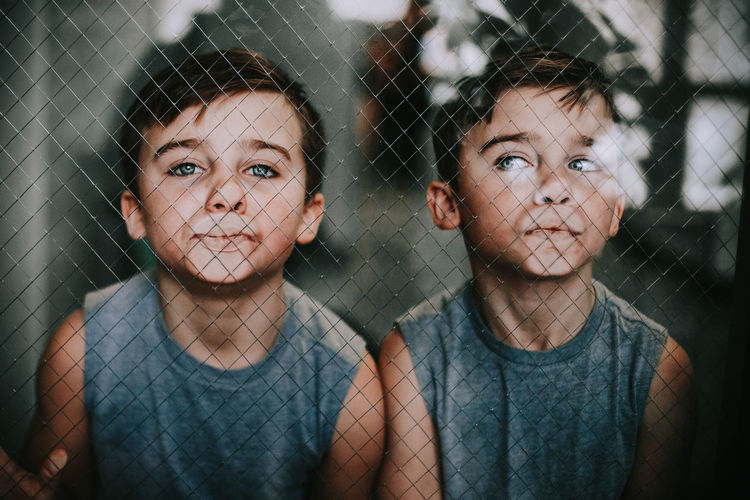 Portrait of boys standing by chainlink fence