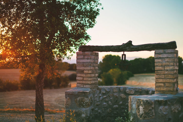 View of old well at sunset