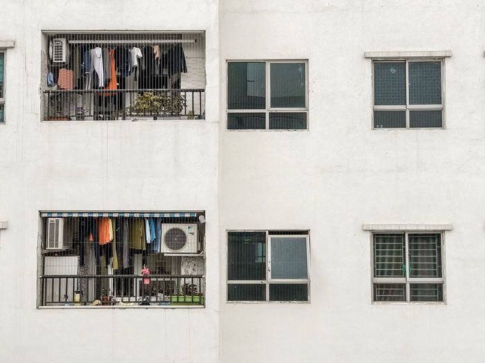 Apartment Buildings Lifestyles Vietnamese Clothes Drying Clothes Hanging Clothes Window Grate Burglar Bars Building Exterior Balconies White Wall Window Building Exterior Built Structure Architecture Building Residential District Day No People Wall - Building Feature Outdoors Glass - Material City Wall Sunlight Full Frame Reflection Pattern Air Conditioner Protection