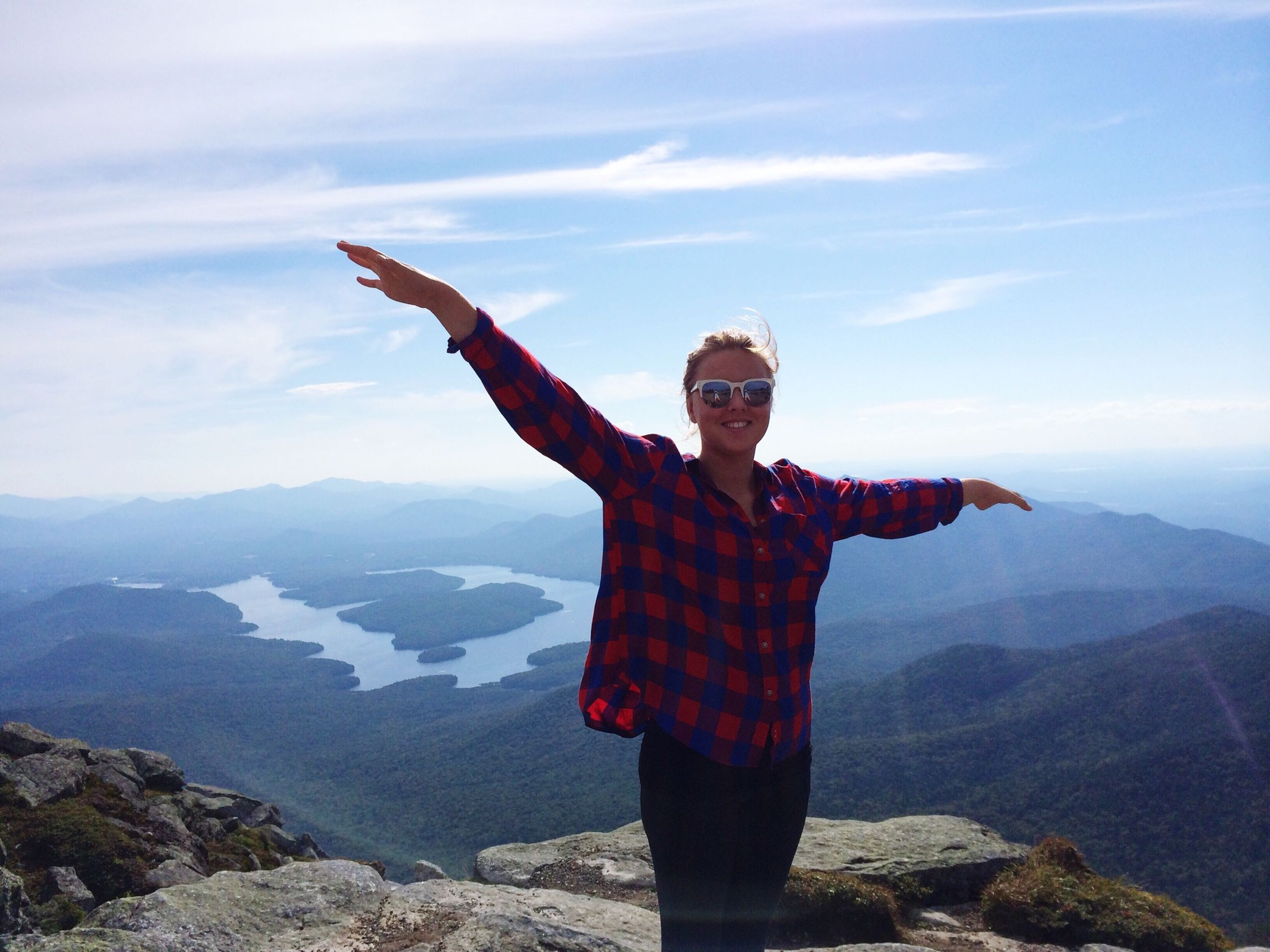 lifestyles, sky, leisure activity, standing, mountain, cloud - sky, arms outstretched, full length, casual clothing, young adult, three quarter length, arms raised, rock - object, tourism, mountain range, freedom, cloud, travel destinations