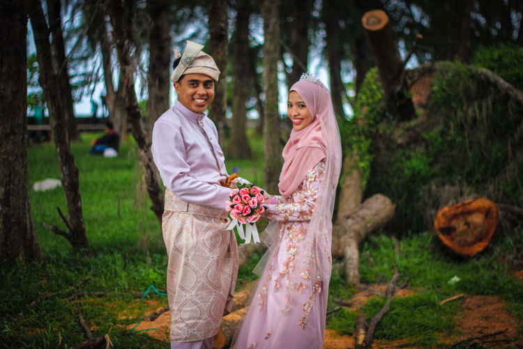 Portrait of smiling couple standing against trees