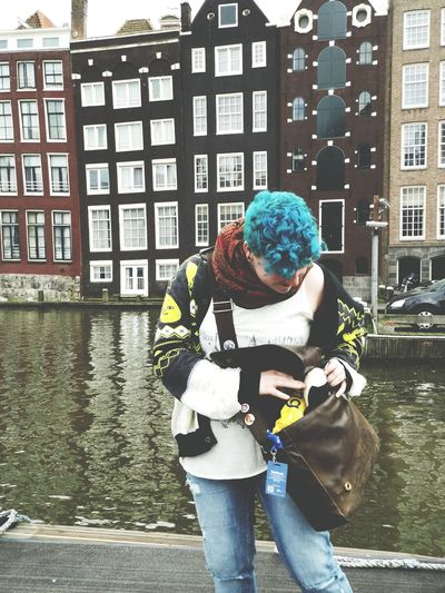 Woman checking her bag while standing near canal against buildings in city