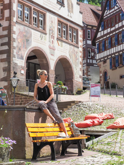 Woman sitting on seat against buildings