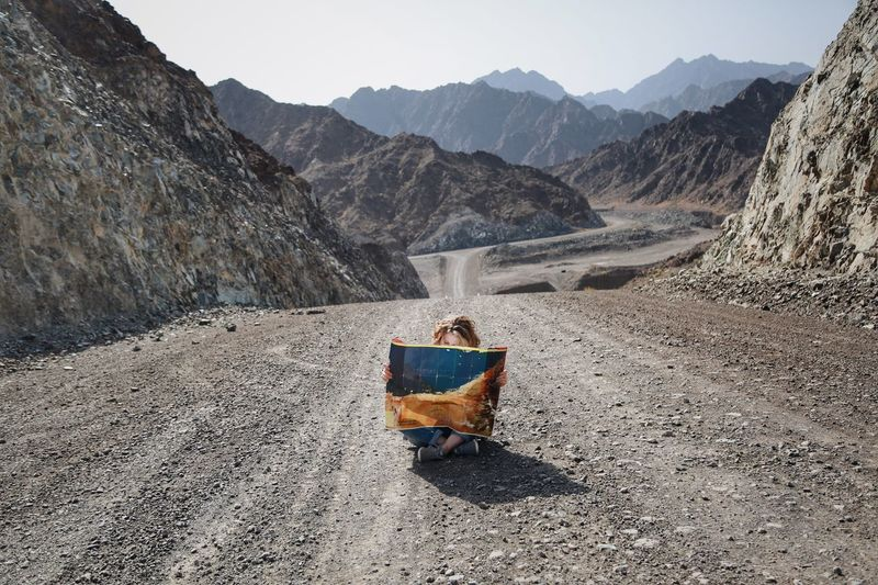 Woman holding map while sitting on road by mountains against sky