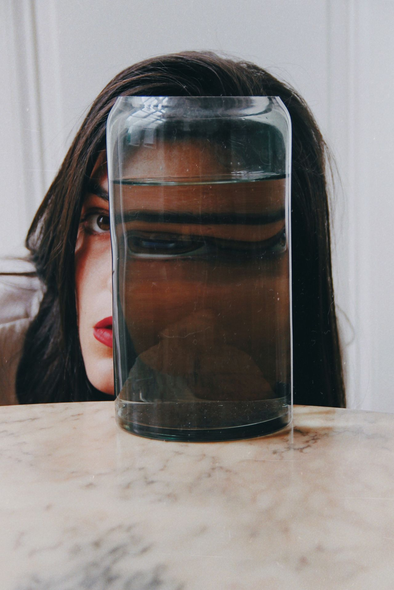 Close-up portrait of young woman with glass on table